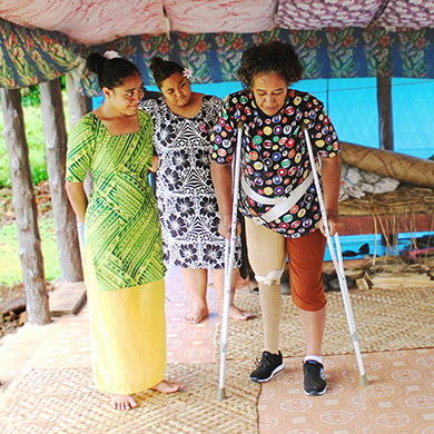 A woman wearing a prosthesis and using crutches walks supervised by two women in bright dresses. All are smiling and focused on the activity.