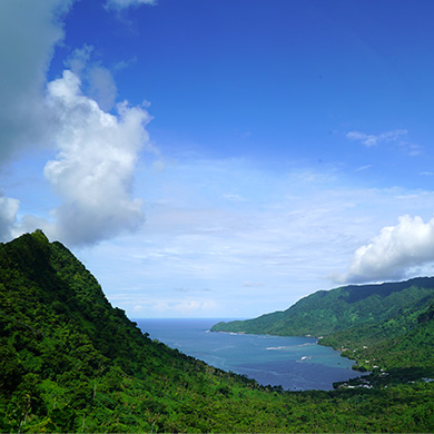 A view of Samoa from the top of a hill. The land is lush and green, the sky and ocean are clear are bright.