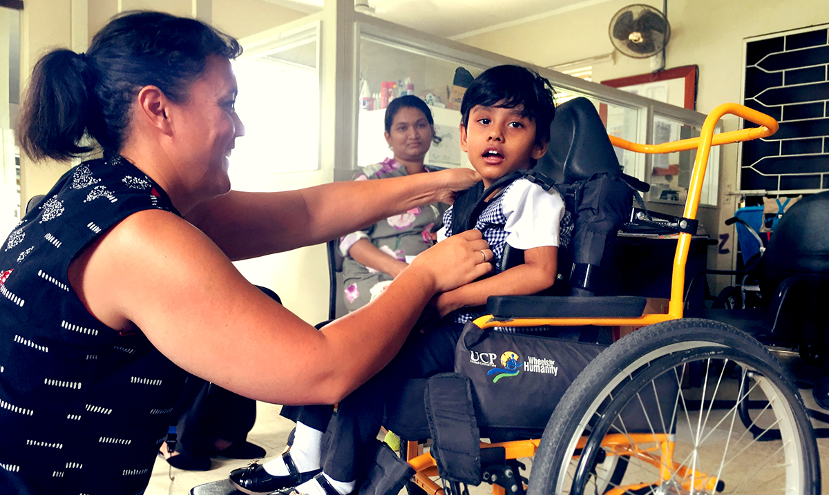 A Fijian girl is being fitted for her wheelchair, which she is sitting in. She is looking at the camera. A therapist from MA checks her chest supports, while a Fijian physiotherapist looks on from behind.