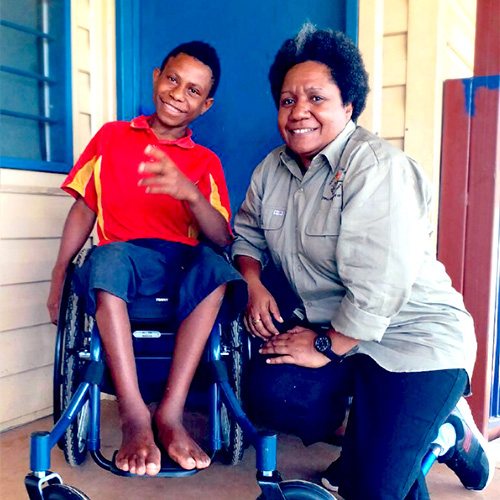 Almah and a young boy using a wheelchair pose for the camera, smiling.