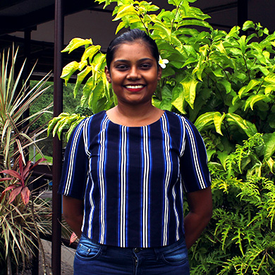 A profile picture of Priyansha standing against a background of lush green plants. She has her hands behind her back and is smiling brightly.