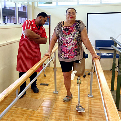 A woman with a prosthetic leg uses parallel bars to help her walk. A man in a colourful apron watches from the side.