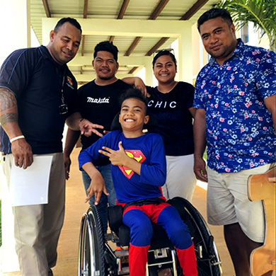 A boy wearing a superman costume sits in his wheelchair and beams at the camera. 3 service staff in dark shirts and his dad in a bright patterned shirt stand behind him, also smiling.