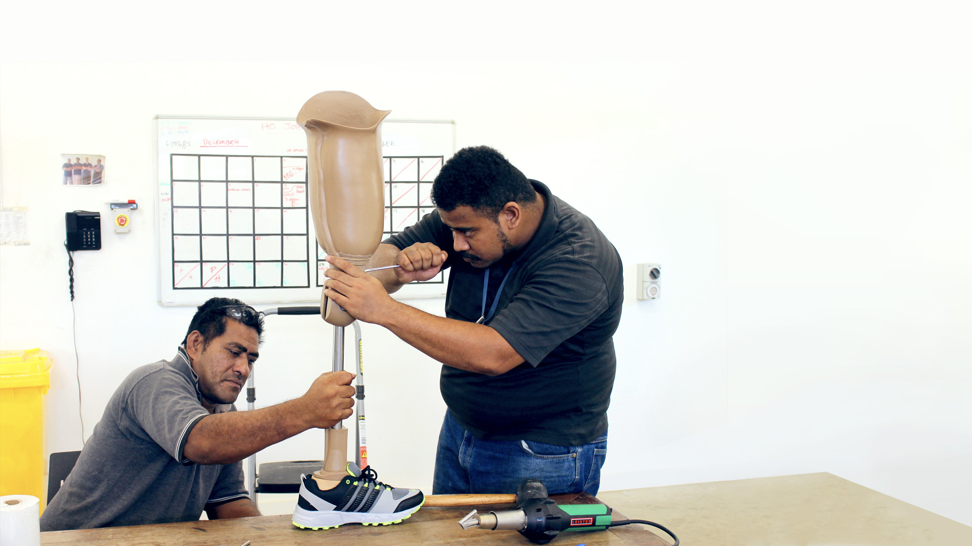 Two men work together to make an adjustment to a prosthetic leg placed upon a workbench. One man sits holding the leg while the other stands, working on it with a tool. Both look very focused.