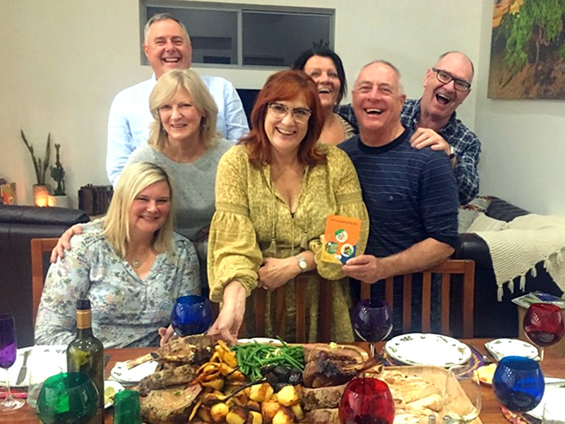 A group of 7 people are gathered behind a table displaying a spread of food. They are smiling brightly at the camera.