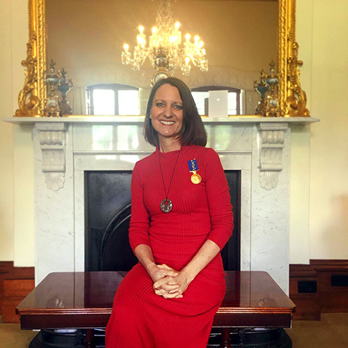 Kylie sitting inside Government House with her medal pinned to her dress, smiling.
