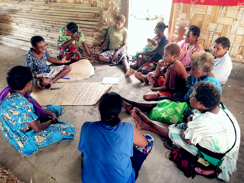 A group of women in colourful clothes sit in a circle on the floor in deep discussion. Pieces of paper with writing on lay in the middle of them.