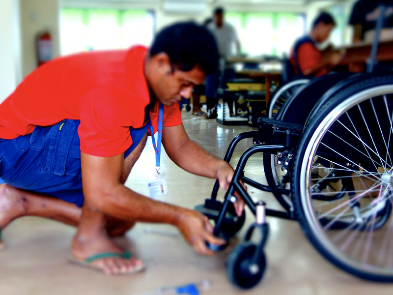 A man bends down to fix the castor wheel of a wheelchair.