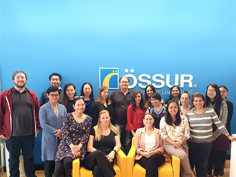 A large group of people are gathered in front of a blue background displaying the logo for Ossur.