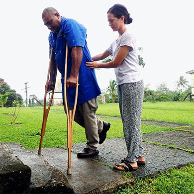 A man using axilla cructhes is supported by a woman with her hands on his waist. They are outside after a recent rain, prepared to go up a few steps.