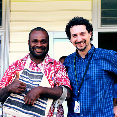 A Pacific Island man and an Australian man stand side by side, smiling brightly in the camera.