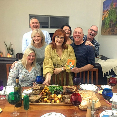 A group of people, all smiling, are gathered in front of a dinner table full of delicious food.