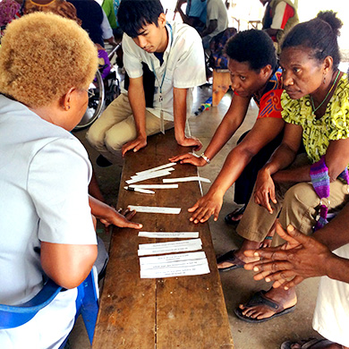 A group of people gather in a circle to discuss things written on paper in front of them.