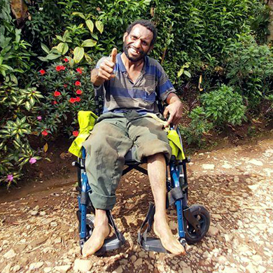A man using a new wheelchair sits outside in the shade of green plants, he smiles widely and gives a big thumbs up to the camera.