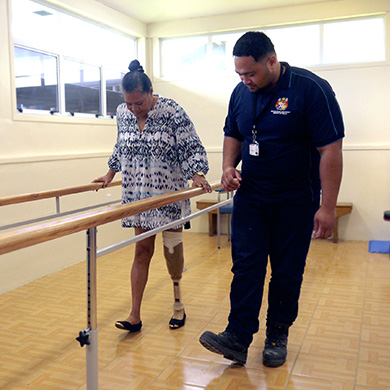 A woman using a prosthetic uses parallel bars to support herself as she walks. A service provider walks beside her. They both have the same foot out.