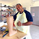 Vai'uli stands at a workbench in an apron, holding a unfinished lower-limb prosthetic. He is smiling brightly and giving a thumbs up.