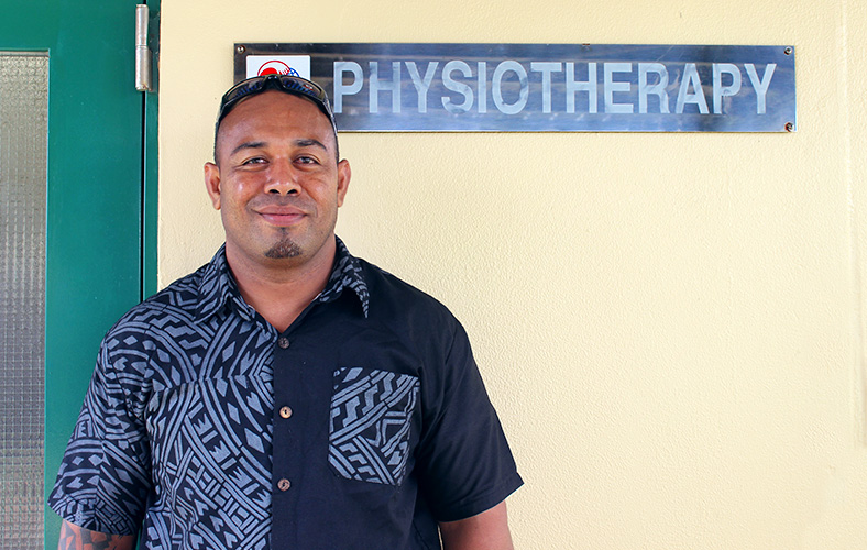Vai'uli stands in front of a sign on a building. It reads 'Physiotherapy'.