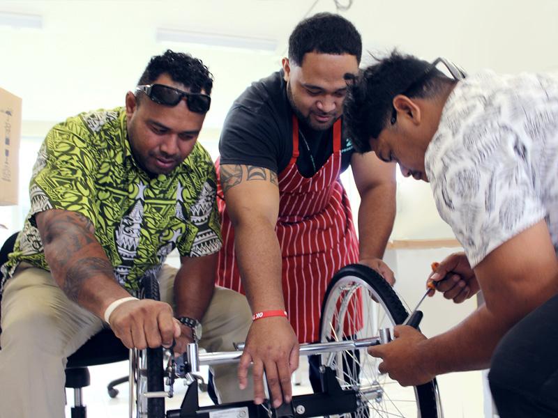 A group of three men make adjustments