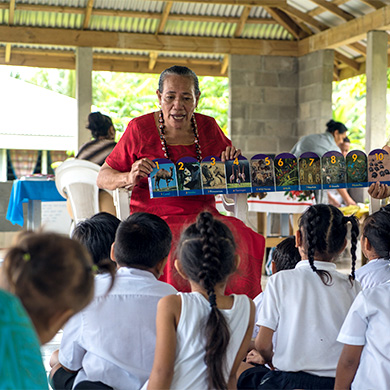 A teacher holds up a set of pictures for a group of attentive children.