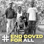 A young girl using a wheelchair sits surrounded by another child, a woman and two men. They smile for the camera. #EndCovidForAll is written along the bottom.