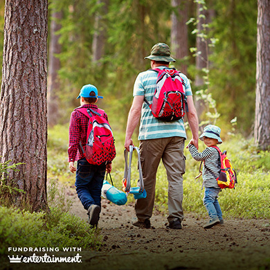 A man and two children walk through a forest. The man holds a child's hand. They are all wearing backpacks.