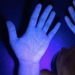 A hand under UV light shown to be clean.