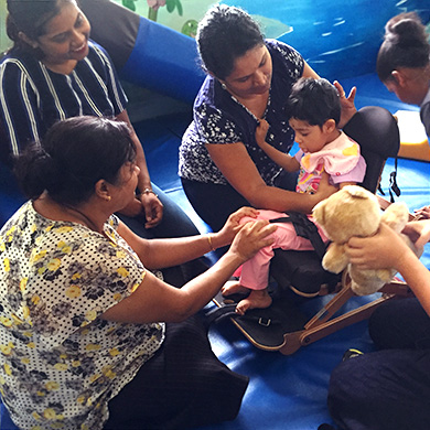 A group of five women help fit a young girl with a new wheelchair.
