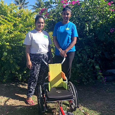Sylvina and Nisha pose outside in the sun smiling with a colourful child-sized wheelchair.