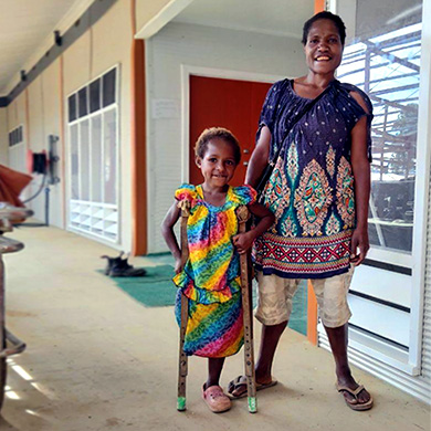 Violet, a young girl in a colourful dress and with a leg amputation, uses crutches to stand next to her mother. Both smile brightly.