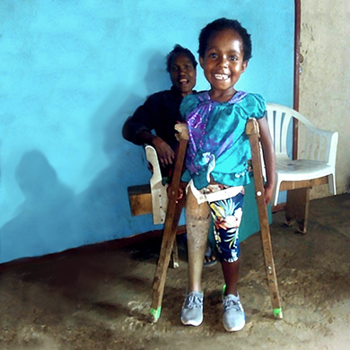 Violet stands in colourful shirt and shorts, using crutches to help her stand with her first prosthesis. Her mother sits behind her. Both are smiling brightly.
