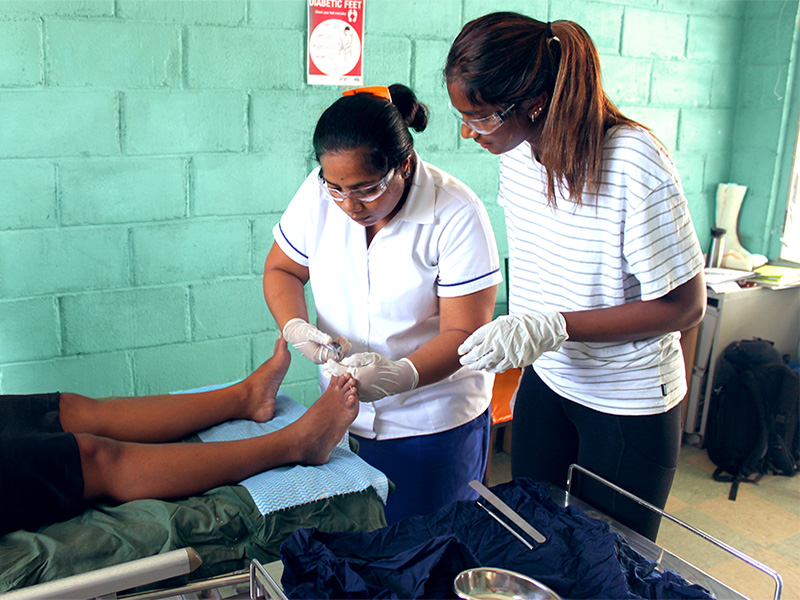 A woman in a service uniform treats a clients foot while another woman in casual clothes watches carefully.