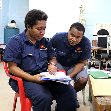 Almah and a man sit reading forms, they are both dressed in the same service uniform.