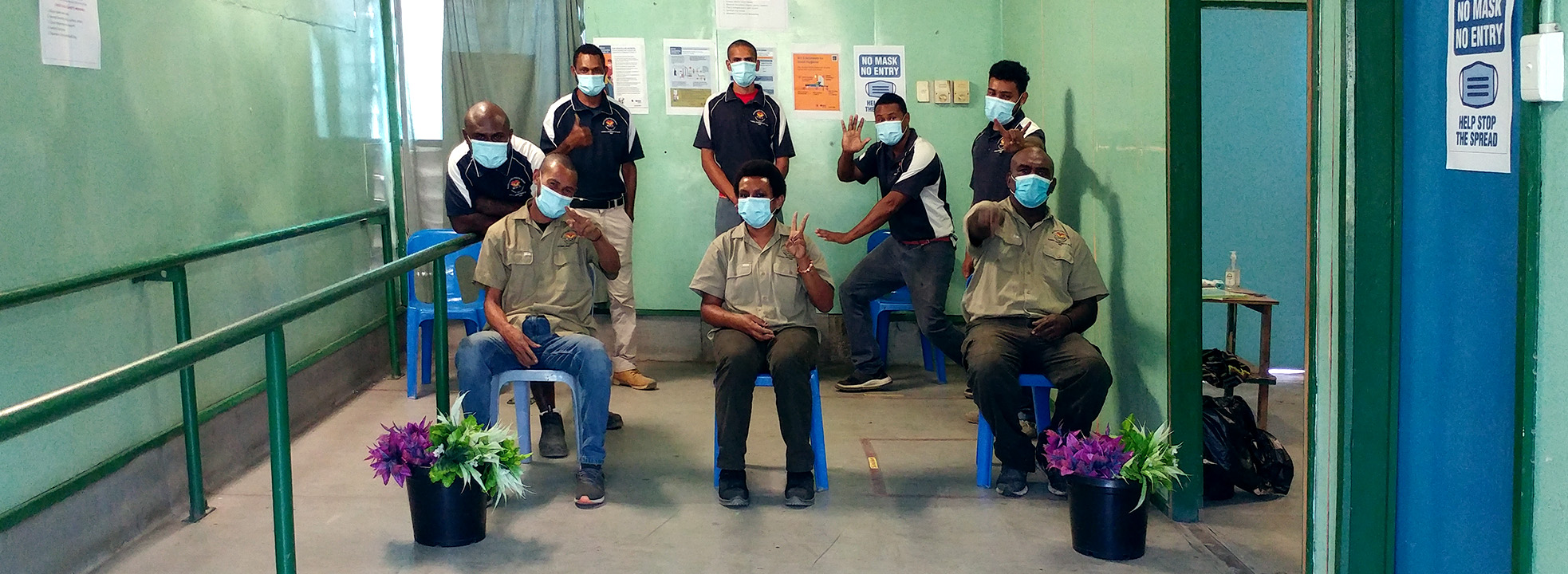 At the end of a long room, eight people pose for the camera humourously, while wearing masks.