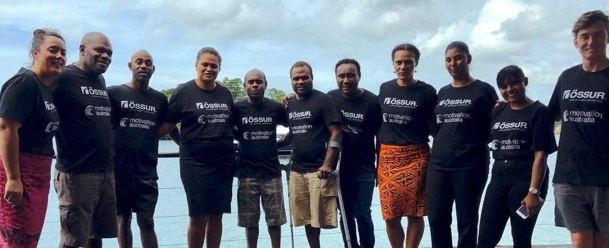 A group of 11 people all wearing the same t-shirts stand in front of the ocean, smiling happily.