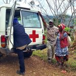 On the side of a dirt road, surrounded by forest and mountains, a large car with a red cross on it has stopped. A man looks in the back of it, while a woman using a thin stick as a cane, and another man wait patiently.