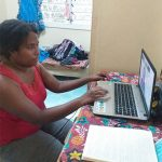 Sharon Juvia, Orthotist, working on laptop with Motivation Australia DFC online training.