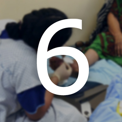A woman dressed in a protective apron and gloves treats a clients foot wound. The number 6 is displayed over the photo.