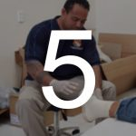 A man reaches out to dress a client's foot. The number 5 is displayed over the photo.