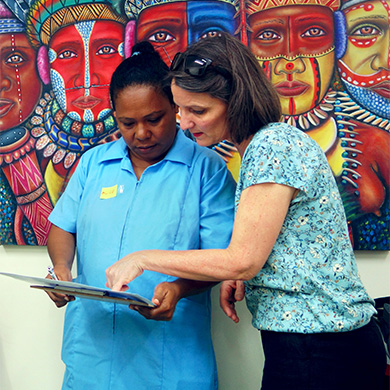 A woman in a nurse uniform holds a clipboard, another woman standing next to her points at it. They are both looking at the clipboard carefully. They stand in front of a colourful painting of people in traditional Papua New Guinea dress.
