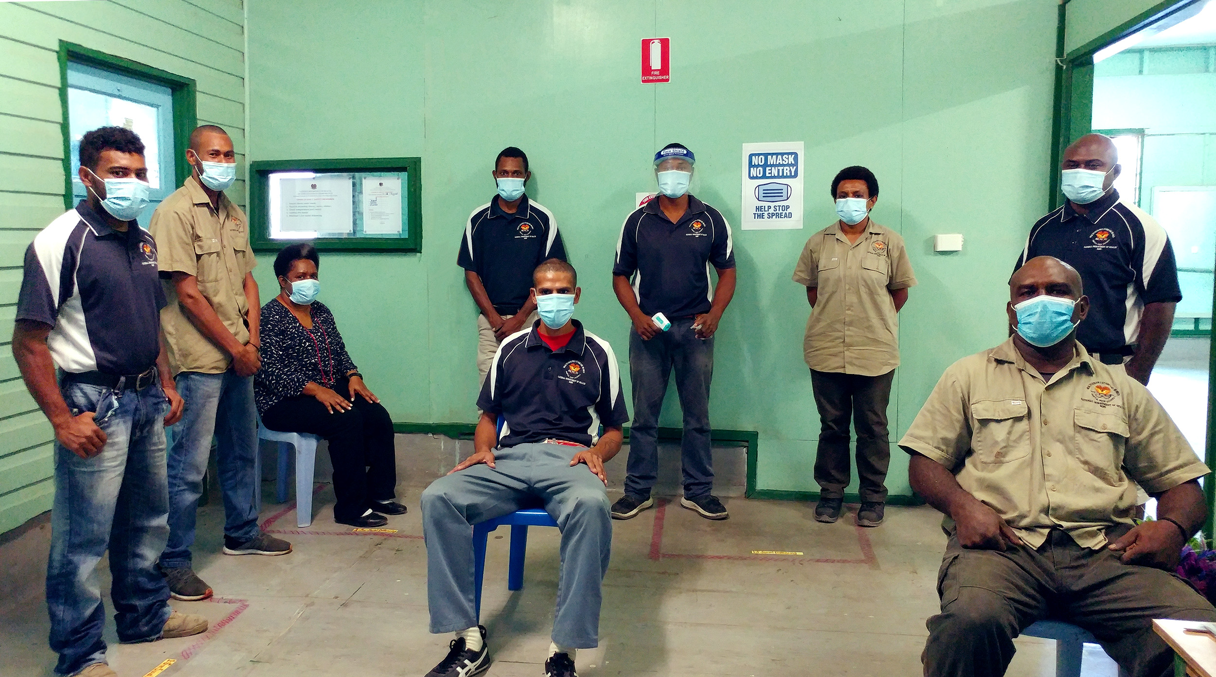 NOPS officers at Port Moresby clinic waiting room, displaying their face masks and social distancing.