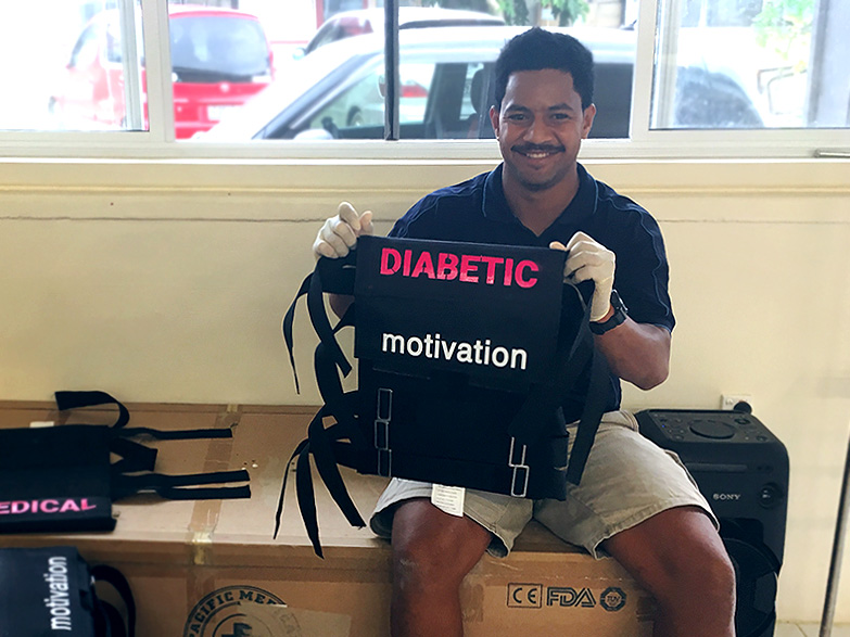 A man sits on cardboard boxes inside a clinic, holding up brand new wheelchair upholstry with the words 'Diabetic' and 'motivation' on them. He is smiling.