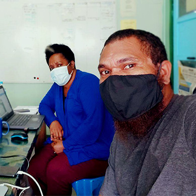 A man and a woman take a selfie. They are wearing facemasks and sat at a desk, socially distanced to work.