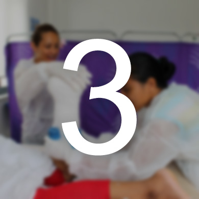 Two women wearing protective gowns wrap a client's foot and lower leg. The number 3 sits over the photo.