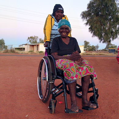 Outside on the red sane, an Indigenous woman using a new wheelchair sits smilign at the camera, another woman is pushing her and smiles too.