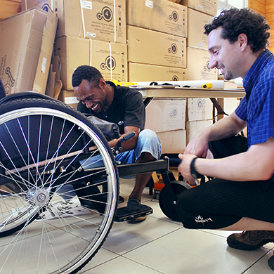 Two men work together to build a wheelchair. One man leans down to adjust something with a smile, the other watches closely, also smiling.