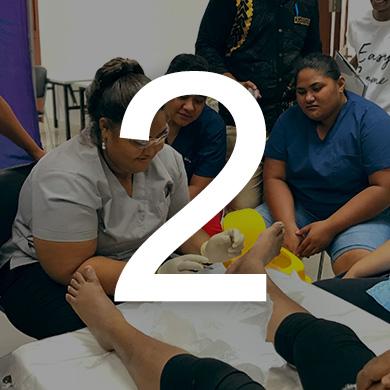A student practices foot wound treatment on a client while a small group watches. The number 2 sits over the image.