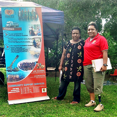 Sommerville and Almah stand together next to a banner for the Mapex Training Institute.