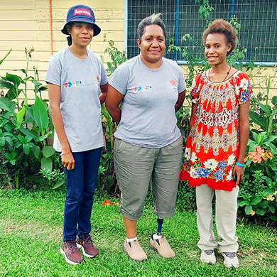 Carolyn, Almah and Joan stand on the grass outside. Carolyn and Almah are wearing the same grey shirts with logos on.