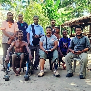 9 people, some sitting and some standing, are outside in the shade smiling at the camera. One man is using a wheelchair and a woman in the centre is using a lower-limb prosthesis.