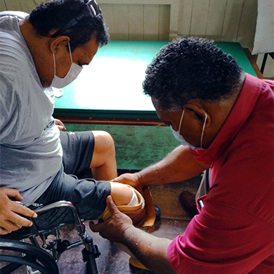 Mosese fitting a below knee prosthesis with a service user. Both are wearing masks.